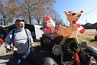 NWA Democrat-Gazette/FLIP PUTTHOFF <br /> CHRISTMAS ON WHEELS<br /> Robert Storey shows Santa and a reindeer seated in a 1930 Model A Roadster that's part of an antique car Christmas display Storey puts together each Christmas season at his home on Price Lane in Rogers. Storey owns and restores classic cars and uses different vehicles for every display. Storey will drive one of his cars in the Rogers Christmas Parade set for 7 p.m. Dec. 7 through downtown Rogers.