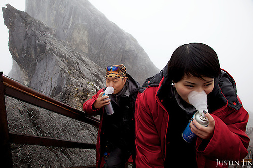 Visitors reach out for their oxygen tanks on the ascend to the 4300 m shoulder of the Yulong mountain near the ancient Lijiang town in Yunnan province, southwestern China.