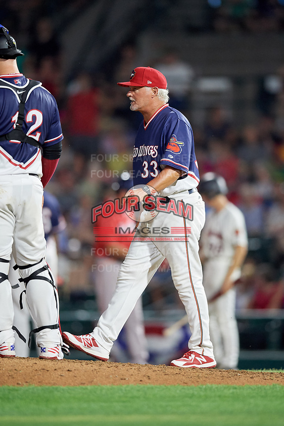Rochester Red Wings pitching coach Stu Cliburn (33) walks to the mound to join catcher Cameron Rupp (12) for a mound visit during a game against the Pawtucket Red Sox on July 4, 2018 at Frontier Field in Rochester, New York.  Pawtucket defeated Rochester 6-5.  (Mike Janes/Four Seam Images)