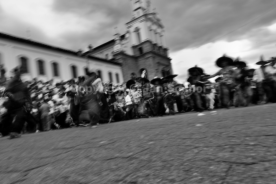 Indians dance furiously during the Inti Raymi (San Juan) festivities in front of the church in Cotacachi, Ecuador, 29 June 2010. 'La toma de la Plaza' (Taking of the square) is an ancient ritual kept by Andean indigenous communities. From the early morning of the feast day, various groups of San Juan dancers from remote mountain villages dance in a slow trot towards the main square of Cotacachi. Reaching the plaza, Indians start to dance around. They pound in synchronized dance rhythm, shout loudly, whistle and wave whips, showing the strength and aggression. Dancers from either the upper communities (El Topo) or the lower communities (La Calera), joined in respective coalitions, seek to conquer and dominate the square and do not let their rivals enter. If not moderated by the police in time, the high tension between groups always ends up in violent clashes.