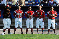 Batavia Muckdogs mascot Homer and players Felix Munoz #27, Felix Castillo #30, Jose Behar #7, and Luis Ortiz #26 stand for the national anthem before a game against the Mahoning Valley Scrappers on June 21, 2013 at Dwyer Stadium in Batavia, New York.  Batavia defeated Mahoning Valley 3-2.  (Mike Janes/Four Seam Images)