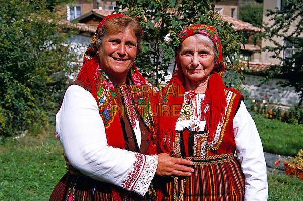 Member of Dobarski Babi Folk Group and tourist on right, Dobarsko, Bulgaria
