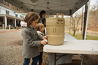 Emma Detwiler, 8, of Chestnut Hill fills her cup with hot apple cider while her brother Tobias, 4, and her mother, Sarah Detwiler taste fire-roasted chestnuts at the Winter in the Wissahickon event hosted by the Friends of the Wissahickon on December 1. (Dave Tavani/for NewsWorks)