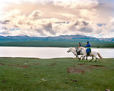 MONGOLIA, Khuvsgul National Park, Nomadic horsemen run their horses along Toilogt Lake