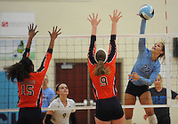 NWA Democrat-Gazette/ANDY SHUPE<br /> Klaire Trainor (22) of Springdale Har-Ber sends the ball over the net as Shanice Erby (15) and C.J. Landram of Rogers Heritage defend Thursday, Sept. 17, 2015, at Wildcat Arena in Springdale. Visit nwadg.com/photos to see more photographs from the game.