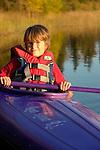 Young man kayaking in Katherine Lake, Riding Mountain National Park Manitoba.