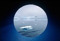 Iceflows seen from boat porthole, Antarctic Peninsula, Antarctica