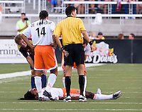 Players look on with concern as Dynamo defender Adrian Serioux lies motionless on the ground after coming down hard on his head in the Real Salt Lake 3-1 win over Houston Dynamo at Rice Eccles Stadium in Salt Lake City, Utah August 19, 2006