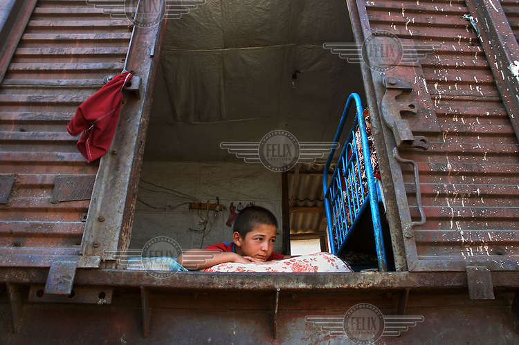 A boy looks out of the doorway of an abandoned railway carriage that is home to his family. It became their home after they fled their village during the 1992 - 1994 war in Nagorno Karabakh.
