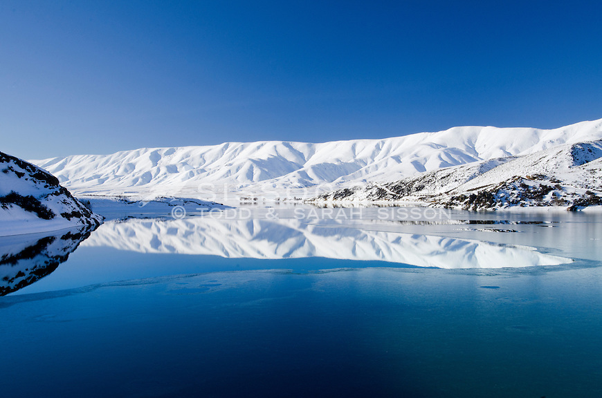 The snow covered Hawkduns in winter reflected in the icy waters of Falls dam, Central Otago, New Zealand