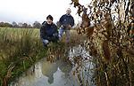 Foto: VidiPhoto<br /> <br /> HEUMEN &ndash; Schouwmeester Erik Kleijn (zonder jas) en medewerker Jonas Moberg van waterschap Rivierenland controleren maandag voor de tweede keer een sloot bij een veehouder in Heumen bij Nijmegen. Bij de herschouw is de zogenoemde B-watergang opnieuw niet in orde. Is dat bij de derde schouw nog steeds het geval, dan wordt de sloot op kosten van de agrari&euml;r schoongemaakt. De 21 waterschappen in het hele land houden tot 31 december de zogenoemde schouwen, waarbij door enkele honderden schouwers gecontroleerd wordt of de slootkanten gemaaid zijn en de watergangen diep genoeg voor de afvoer van regenwater. De A-watergangen vallen onder het beheer van de waterschappen, maar de B-watergangen moeten door de eigenaar onderhouden worden. Doordat de weersomstandigheden steeds extremer worden en er steeds meer water valt, worden sloten en spaarbekkens steeds belangrijker. Volgens Kleijn gebeurt het maar zelden dat het waterschap zelf een bedrijf moet inhuren om de taak van de eigenaar over te nemen en dat er boetes worden uitgedeeld. Het schouwen gebeurt tussen 1 november en 31 december.