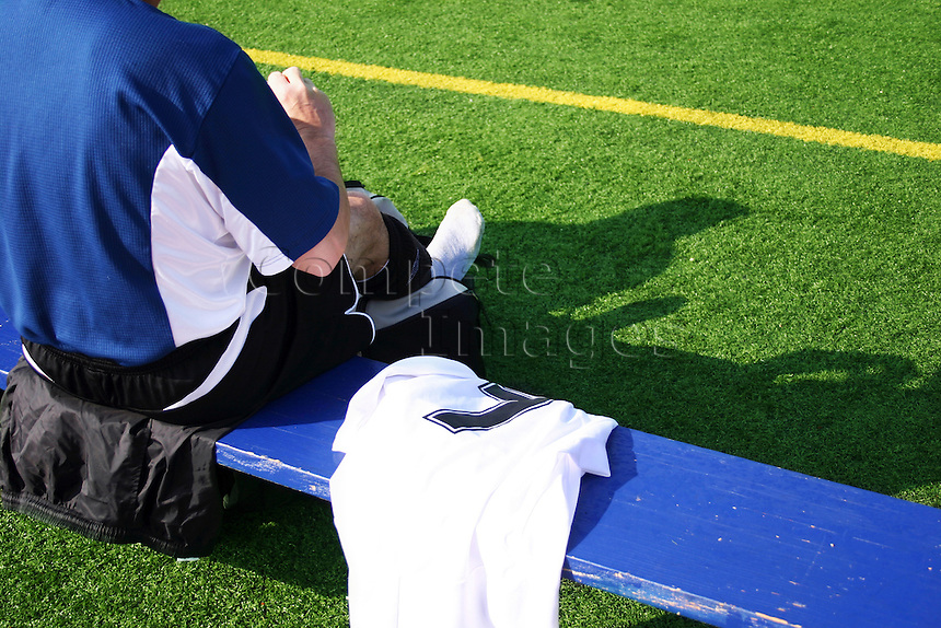 Footballer sits on bench and changes for a football match