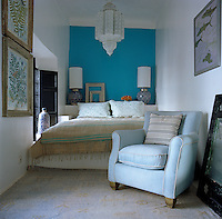 This narrow bedroom is furnished with both traditional  Moroccan and contemporary furniture and has a bright turquoise wall