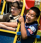 "Photo by Phil Grout..Timothy Niles (front) and his buddy, Zack Miles, delight in the wild ride aboard the v""Bunny Bucket"" at the Bond Mill Elementary School carnival."