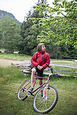 CANADA, Vancouver, British Columbia, boy stands stands with his bike on Gambier Island, in the Howe Sound