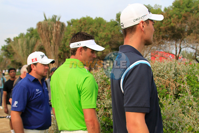 Charl Schwartzel has to search for his ball in the bushes after driving off on the 13th hole with help from Martin Kaymer and Graeme McDowell during Day 3 Saturday of the Abu Dhabi HSBC Golf Championship, 22nd January 2011..(Picture Eoin Clarke/www.golffile.ie)