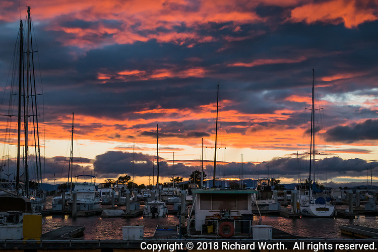 A mixture of glowing orange and shades of gray clouds over the sailboats at the San Leandro Marina after the first storms of the season passed through the San Francisco Bay area.