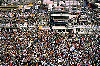 LE MANS, FRANCE - JUNE 11: Spectators swarm across the pit lane and front straight as the winning drivers celebrate on the podium following the 24 Hours of Le Mans at the Circuit de la Sarthe in Le Mans, France, on June 11, 1989.