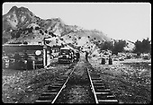 Shed which possibly a station alongside railroad track and auto parked beside track with passengers.<br /> D&amp;RGW