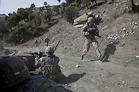 US Army Soldiers from Viper Company 126, 2nd Platoon, run for cover and return fire after being attacked on a foot patrol near Atabad in the restive Korengal Valley. The patrol was to meet with key tribal leaders in the village, where they received intelligence of an imminent attack.