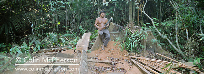 An Amazonian villager with a machete sitting in a clearing in the rainforest where he is sustainably extracting wood for his community's use. The Floresta Nacional do Tapajos (FLONA), a 6500 km2 protected reserve, was home to several small communities which lived on the banks of the Rio Tapajos river. The communities did not have electricity or running water and access to the villages was by unpaved dirt roads from Santarem and Highway BR163 but they were protected from illegal logging and deforestation which took place to facilitate cattle ranching and growing soy beans for export.