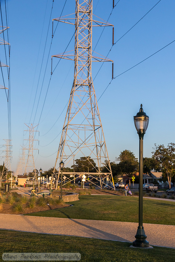 Late afternoon light makes the electrical towers and light poles  cast dramatic shadows across the State Street Park as a woman pushses a stroller down the pedestrian pathway.