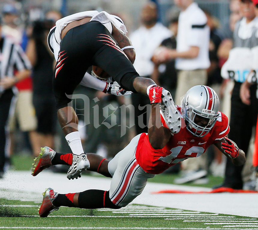 Ohio State Buckeyes cornerback Doran Grant (12) trips up Cincinnati Bearcats wide receiver Nate Cole (84) in the first quarter of a football game between The Ohio State Buckeyes and the University of Cincinnati Bearcats on Saturday, September 27, 2014 at Ohio Stadium in Columbus. (Columbus Dispatch photo by Fred Squillante)