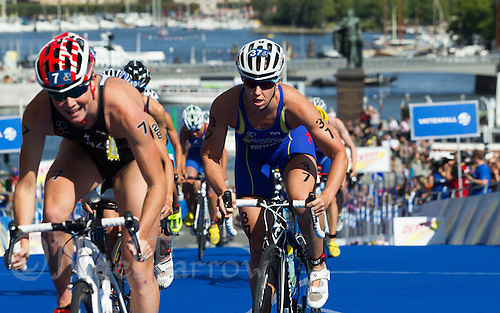 24 AUG 2013 - STOCKHOLM, SWE - Lisa Norden (SWE) (right) of Sweden starts the next lap of the bike during the elite women's ITU 2013 World Triathlon Series round in Gamla Stan in Stockholm, Sweden (PHOTO COPYRIGHT © 2013 NIGEL FARROW, ALL RIGHTS RESERVED)