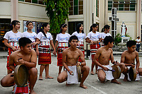PHILIPPINES, Mountain Province, Cordilleras, Bontoc, youth group performes traditional tribal dance of Igorot culture in front of church