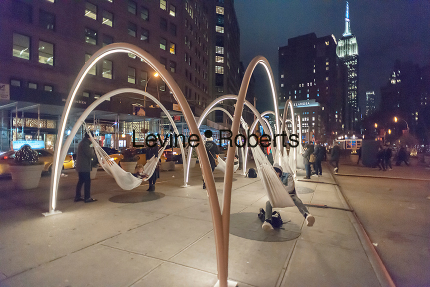 "Visitors to Flatiron Plaza in New York on Tuesday, November 22, 2016 interact with ""Flatiron Sky-Line"" created by architectural firm LOT. The Christmas installation is the centerpiece of the Flatiron 23rd Street Partnership's  holiday programming. The ten illuminated arches with hammocks suspended underneath engage visitors to relax and to contemplate the architectural wonders of the neighborhood, specifically the Flatiron Building. (© Richard B. Levine)"