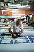 Local Rajasthani printer prints designs on fabric using wooden blocks at a factory in Jaipur, Rajasthan, India.
