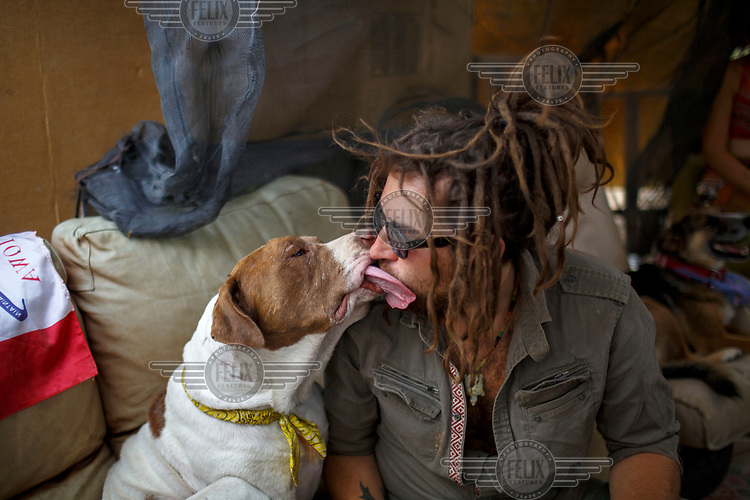 Mike is licked by his dog Zeus in Slab CIty, a squatters' camp about 190 miles southeast of Los Angeles. Mike spent three mopnths in jail for possession before moving to the camp. <br /> <br /> 'My dog suffered the worst. He was taken away from me when I was doing my time in jail. I tracked him down and finally found him couple months ago in Georgia. He is almost six years old. When I got him back, he had no teeth anymore. It was frustrating being in jail. I am a vegan and I didn't get any food preference. Unless you have a religious distinction, they won't approve your dietary needs. I told them I am of the religion of love and light. I was on hunger strike for six weeks. The moment I came into acceptance, they let me go. My dog is going to be famous one day; he sings for me.' <br /> <br /> Slab City, known as The Slabs, is named for its areas of concrete where for many years, since the military based closed, people have parked their RVs as they travel south for the winter. There is also a permanent community of 'Slabbers', around 200 people, who have established themselves living free in the Sonoran Desert where temperatures can reach 48 Celsius in the summer and, while there is no rent, there is also no water, electricity or services. Slabbers are an eclectic bunch often escaping poverty but also holding in common the desire to escape the rules and order of society in what they like to call 'the last free place on earth'.