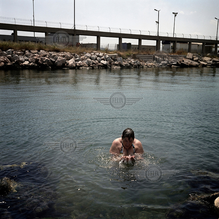 A woman swims in the sea off Elefsina with the Skaramagas shipyard in the background. The area of sea around the town is not safe for swimmers as it is heavily polluted by waste from nearby shipyards, oil refineries, cement factories and tanneries.