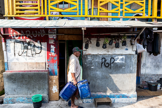 13 August 2019, Jakarta, Indonesia: Water seller Pak Sampras delivers water in plastic barrels to homes in Muara Baru, North Jakarta. There is a severe lack of water facilities that the local poor population has access to. Water is hauled in each day by motorcycle and trucks and by hand to allow residents of the kampungs (village) to buy it for washing and to do laundry. Separate water is needed for drinking. The Jakarta Governor is proposing a program to send in trucks of water for the locals to get for free to ease their plight. They are living in villages below the seawater line on the coast of Jakarta that is sinking faster than anywhere else in the world.They have the position of being surrounded by water yet not having access to clean supplies. Picture by Graham Crouch/The Australian