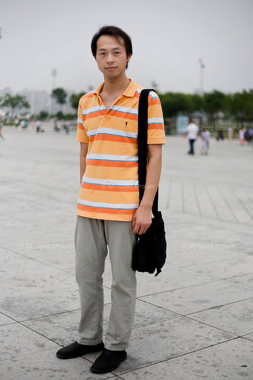 Huangzhongwei, a waiter, age 30, poses for a portrait in Beijing. Response to 'What does China mean to you?': 'My country.'  Response to 'What is your role in China's future?': 'To be a friend.'