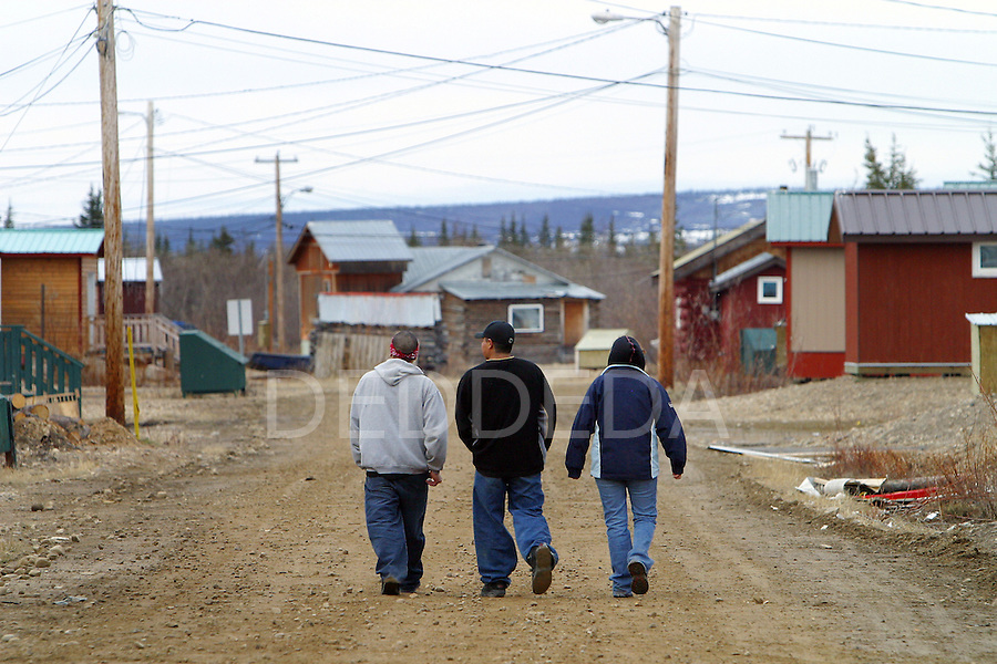 Three Vuntut Gwitchin teenagers walk down a dirt road in the remote aboriginal community of Old Crow, Yukon Territory, Canada.