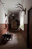 A panelled corridor is lined with hunting trophies