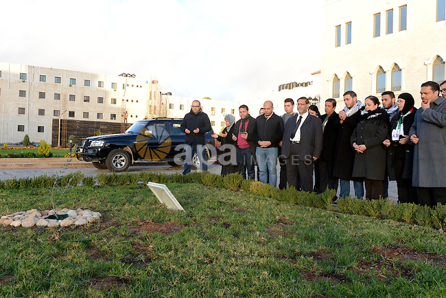 Members of the family of late Palestinian Cabinet member Ziad Abu Ain, visit the last olive tree sapling that he was planted before his death, after it was transferred to al-Moqata'a, the headquarter of Palestinian President Mahmoud Abbas, in the West Bank city of Ramallah, December 14, 2014. A minister in the Palestinian Authority, Ziad Abu Ein, has died while leading a group of Palestinians last Wednesday to plant olive trees near the village of Turmusayya, after being beaten by Israeli security forces and inhaling tear gas during a protest in the occupied West Bank, witnesses said. Photo by Thaer Ganaim