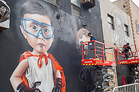 "Artists work on their murals in Bushwick, Brooklyn in New York during the annual Bushwick Collective Block Party on Saturday, June 4, 2016. Music and partying brought some but the real attraction was the new murals  by ""graffiti"" artists that decorate the walls of the buildings that the collective uses.  (© Richard B. Levine)"
