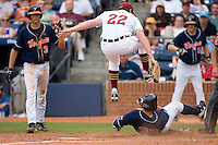 John Gast #22 of the Florida State Seminoles leaps over a sliding Franco Valdes #33 as he scores on a wild pitch at Durham Bulls Athletic Park May 24, 2009 in Durham, North Carolina. The Virginia Cavaliers defeated the Florida State Seminoles 6-3 to win the 2009 ACC Baseball Championship.  (Photo by Brian Westerholt / Four Seam Images)