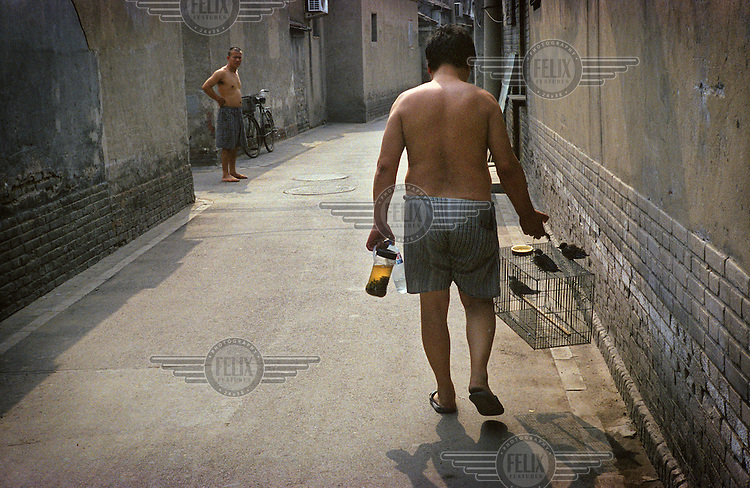 A man carries a birdcage through a hutong neighbourhood. The traditional hutong areas of Beijing are being systematically demolished to make way for new modern developments in the city.