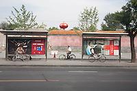 Cina, Pechino, biciclette.  paesaggio urbano con un ciclista e due biciclette parcheggiate ad una fermata del bus <br /> China , Beijing , bicycles . cityscape with a cyclist and two bicycles parked at a bus stop