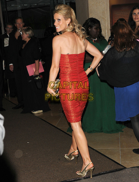 CHERYL HINES .Leaving the 67th Golden Globes held at The Beverly Hilton Hotel in Beverly Hills, California, USA..January 17th, 2010 .globe departures full length red orange strapless dress clutch bag sparkly gold shoes hand on hip looking over shoulder back behind rear.CAP/DVS.©Debbie VanStory/Capital Pictures