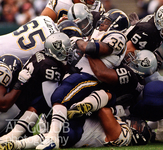 Oakland Raiders vs. San Diego Chargers at Oakland Alameda County Coliseum Sunday, November 14, 1999.  Raiders beat Chargers  28-9.  Oakland Raiders defensive end James Harris (93) and defensive end Darrell Russell (96) tackle San Diego Chargers running back Jermaine Fazande (35).