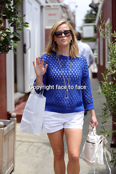 Reese Witherspoon gets photo-bombed by a paparazzo while out shopping at the Brentwood County Mart. The pap was sad that he didn't get a picture so he left his imprint by jumping the picture. Reese is wearing summerly white shorts with white Proenza Schouler bag and blue crochet sweater. Los Angeles, California on July 7, 2013<br /> Credit: Vida/face to face