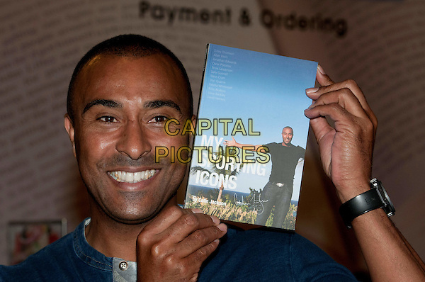 Colin Jackson booksigning at Selfridges, London.  British sprint and hurdling athlete who became world champion three times, signs copies of his book 'My Sporting Icons', to mark the London 2012 Olympics. Jackson originally published his memoirs, 'The Autobiography of Colin Jackson', in 2003. Selfridges, London, England..August 1st, 2012.headshot portrait blue top  book  .CAP/BF.©Bob Fidgeon/Capital Pictures.