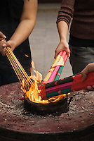 hands of people lighting incense in Chinese temple, Shanghai, China
