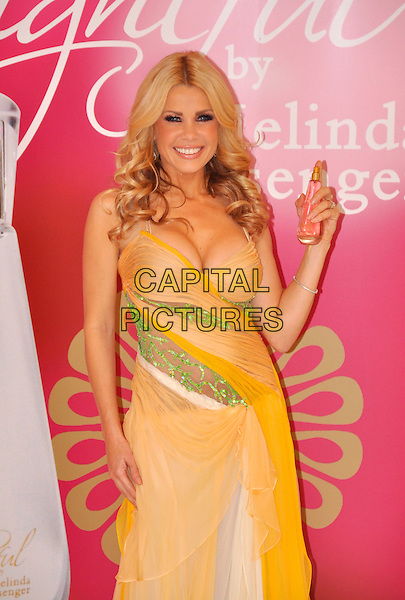 "MELINDA MESSENGER.Launch her new fragrence ""Delightful"" at Vanilla, London, England..December 2nd, 2008 .perfume half length 3/4 yellow orange green sheer dress cleavage bottle .CAP/TTL.© TTL/Capital Pictures."