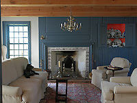 Contemporary seating contrasts with blue-painted restored panelling in the living room