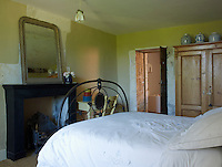 A guest bedroom is simply furnished with a wrought-iron bed and a pine wardrobe